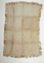 Mat made from a white plant material. The leaf strips are diagonally plaited. Mat edges are fringed.
