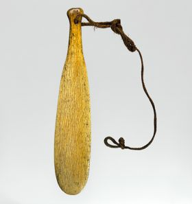 club made of whalebone, with hole drilled at the grip end, with strap made of plaited cord.