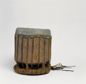 Standing drum with zig-zag lashing. Drum skin made from shark skin fastened with plaited cord of coconut fibres stretched from the cover to the ring-like pedestal.