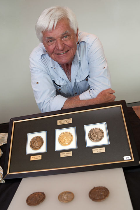 Colour photograph of a man resting with folded arms on a table. In front is a framed set of three circular medals. Another three medals are in the foreground.