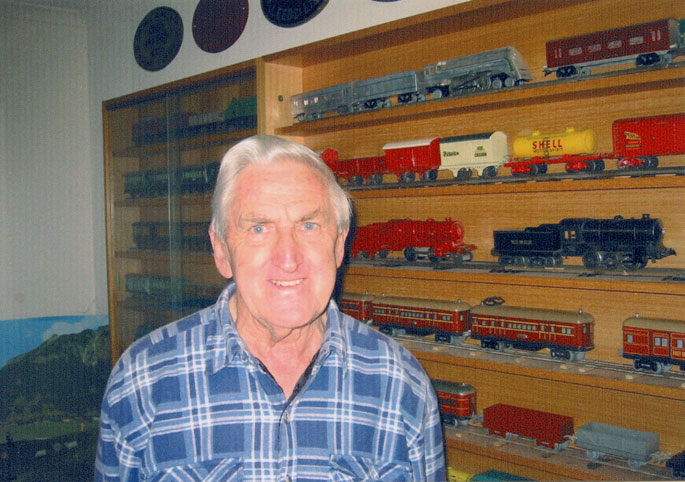 A colour photograph of Bruce Macdonald with his train collection.