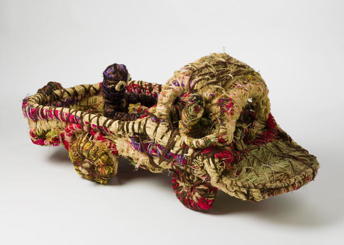 A sculpture depicting a truck with two people in the cabin and one person travelling on the back . The sculpture is made of grass with woven plant material dyed in different colours and strands of wool.