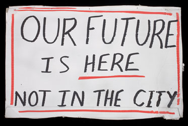 Photograph of a handmade sign on a white piece of card, with a border of red. Black handwritten text reads 'OUR FUTURE IS HERE NOT IN THE CITY'.
