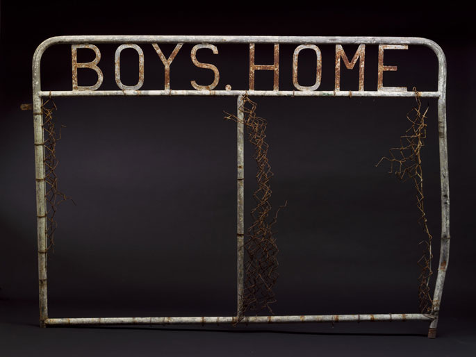 A metal gate with segments of wire attached to the sides and centre. Metal letters welded to the top read 'BOYS HOME'.