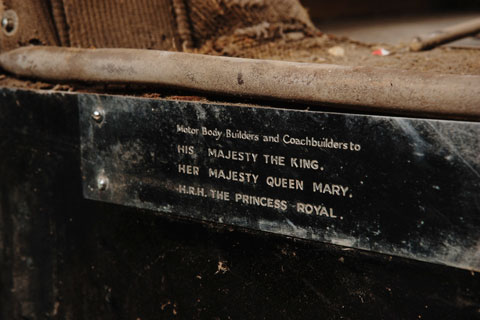 A metal plate attached to the bodywork of an historic vehicle. Text on the plate says 'Motor Body Builders and Coachbuilders to His Majesty The King, Her Majesty Queen Mary, H.R.H. The Princess Royal.'