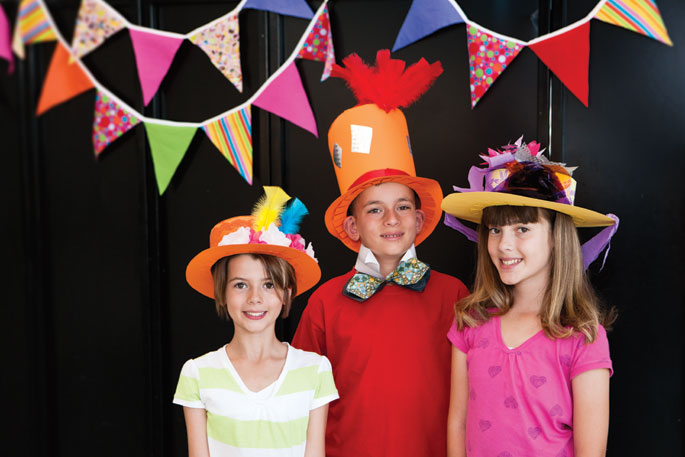 Three children dressed in colourfully decorated top hats.