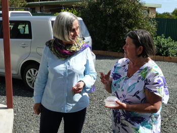 Two women talking. A white SUV can be seen in the background.