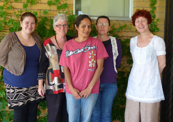Five women standing in front of the brick wall of a house covered in climbing vines.