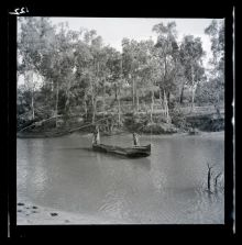 A black and white photographic negative that depicts an Aboriginal child and adult standing in a canoe on a river.