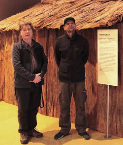 Two men stand in front of a bark hut on display at the museum.