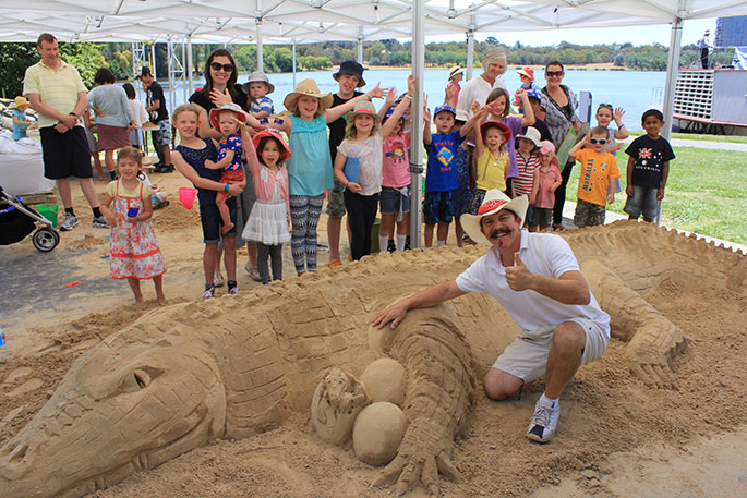 Sand sculptor Tutti Bonacci poses with his creation in front of an enthusiastic group of supporters, 26 January 2014.