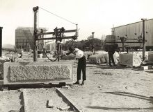 Black and white photograph of two men working on large granite blocks.