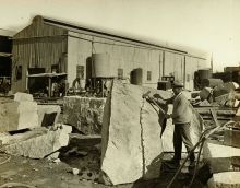 A worker uses wedges and a hammer to split a granite block.