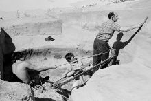 Black and white photograph of three men working in a pit in a desert scene. Two men pull on ropes supporting a metal structure where a third man stands with a trowel in his extended right arm.