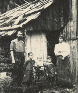 Black and white photo showing a man, woman and three young children standing in front of a slab hut.