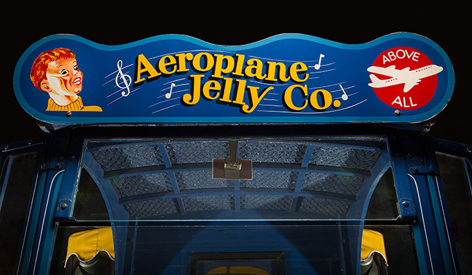 Top section of the front of a truck showing glass windscreen and a blue board painted with text 'Aeroplane Jelly Co', 'Above All' and a whistling boy.