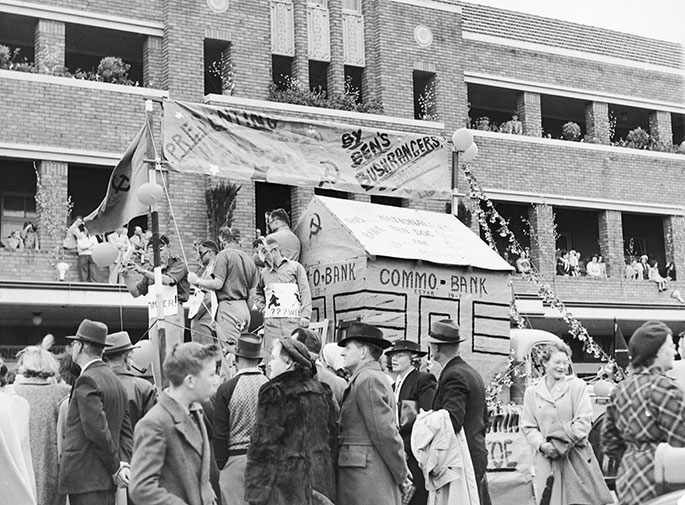 A float with a mocked-up building with the words on 'Commo Bank' painted on the side. It is partly obscured by crowds in the street.