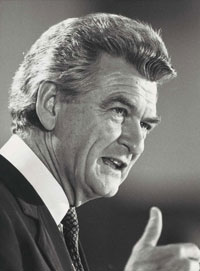 Black and white three-quarter profile photo of Hawke speaking publicly