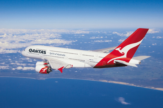 Qantas aircraft in flight over coastline.