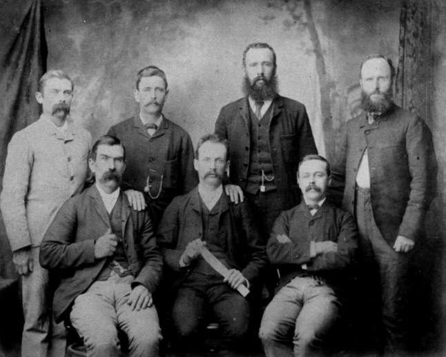 Seven men in a studio group photograph, staring unsmiling at the camera. The name of organisation has been hand-written on the top frame.