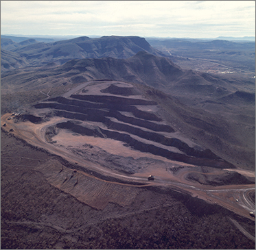 Aerial photo of an open cut mine carved out of the side of a large hill. Massive mining trucks are visible on the perimeter road. Unsullied countryside and mountains in the foreground and background.