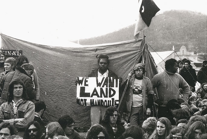 Aboriginal man standing in front of tent holding up sign saying 'We want land not handouts'. He is surrounded by a dozen or so other protesters.