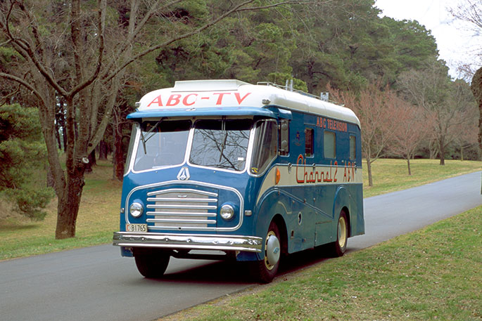 Blue van on a country road. ABC TV is painted on the front above the windscreen.