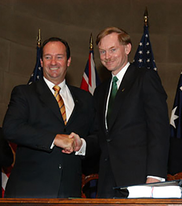 Vaile and Zoellick pose for the cameras shaking hands and smiling. Behind them are a series of Australian and US flags along with a man and a woman smiling and clapping