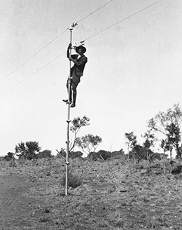A black and white photo taken in the 1920s of a man who has climbed up to the top of a pole
