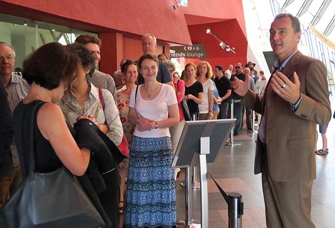 Museum director Mat Trinca welcomes a queue of visitors.