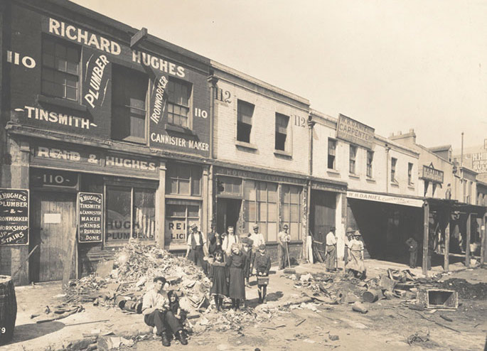 A dozen or so people pose in front of shop fronts amid rubbish that has been removed from the interiors of buildings