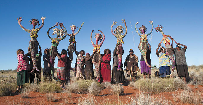 Group of women in a desert holding large grass figures above their heads. <em>Kungkarrangkalnga-ya Parrpakanu — Seven Sisters Are Flying</em> with their makers, the Tjanpi Desert Weavers from Papulankutja, 2015.