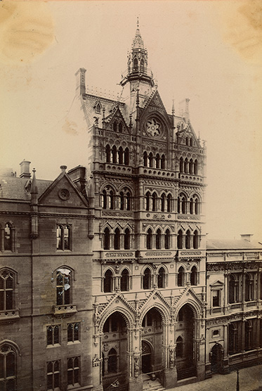 An ornate gothic building seven or eight storeys high with lower buildings on either side