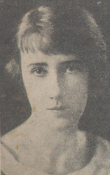Photograph of a dark-haired woman gazing, unsmiling, at the camera