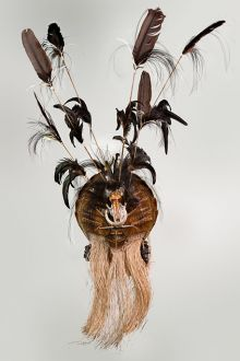 Cultural mask with yellow ochre and white tones, feathers and other materials.