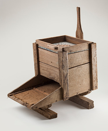 Studio photo of a simple contraption made of timber. It appears to be essentially a box with a tray extending from one side, and a handle from the other. On the top surface of the box is a metal sheet punctuated with holes.