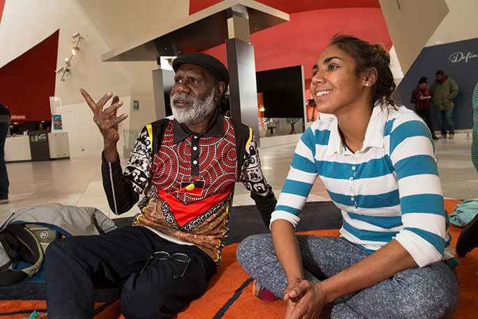 Elderly man sitting and in conversation with young woman