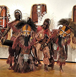 Four men in tribal costumes, standing in front of large masks mounted on a gallery wall