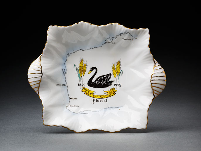 Ceramic plate with gold trim and an illustration of a black swan on a map of Western Australia