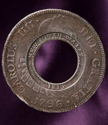 studio photo of silver coin with missing centre. The original Spanish imprinting in Latin is visible around the outside rim, while the words five shillings have been imprinted around the inside rim