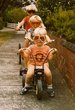Three children on bicycles and wearing goggles