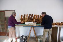 Two men stand at a bench adjusting large bones.