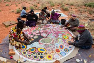 A group of women sits around a circular canvas in the desert