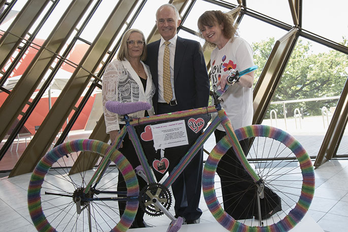 Two women and a man standing behind a bicycle covered with rainbow-coloured yarn.