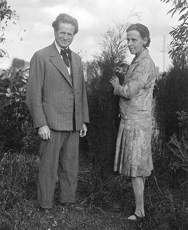 An old black and white photo of a middle-aged couple outdoors.
