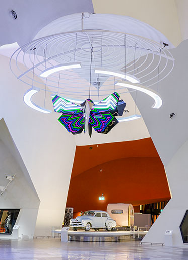 A vast atrium with a brightly-coloured sculpture suspended from the ceiling and a Holden car, with pink caravan, at the centre of frame.