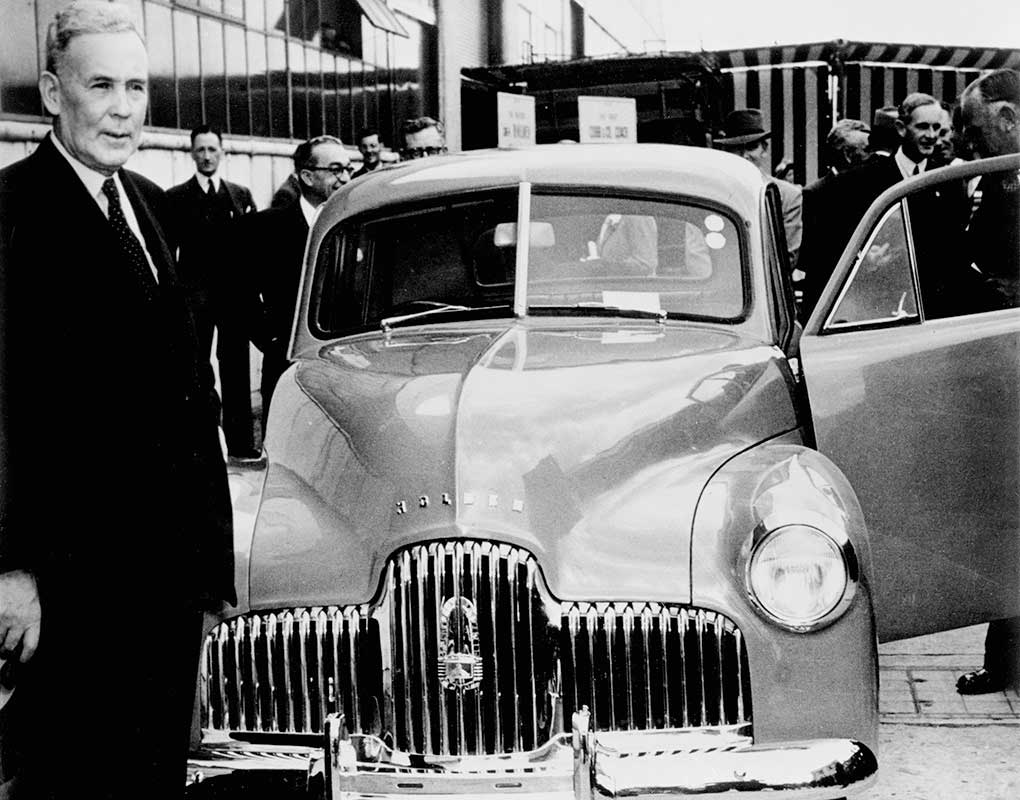 Black and white photo of Ben Chifley with a Holden car.