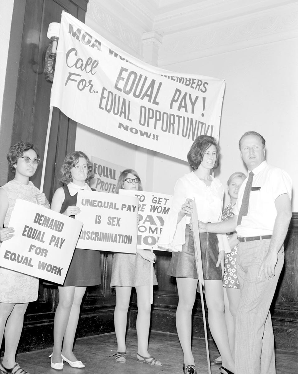Four women holding up placards say such things as 'Call for equal pay, equal opportunity now! - click to view larger image