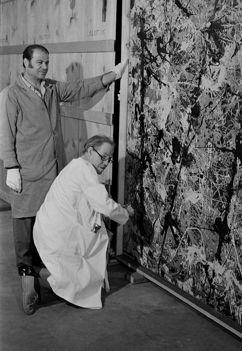 Black and white photo of two men in protective coats, one standing, one crouching, by Blue Poles, part of which is visible. Three of its distinctive poles can be seen. These are thick, dark more or less vertical lines of splattered paint. These have been painted over a splattered arrangement of different coloured paint. - click to view larger image