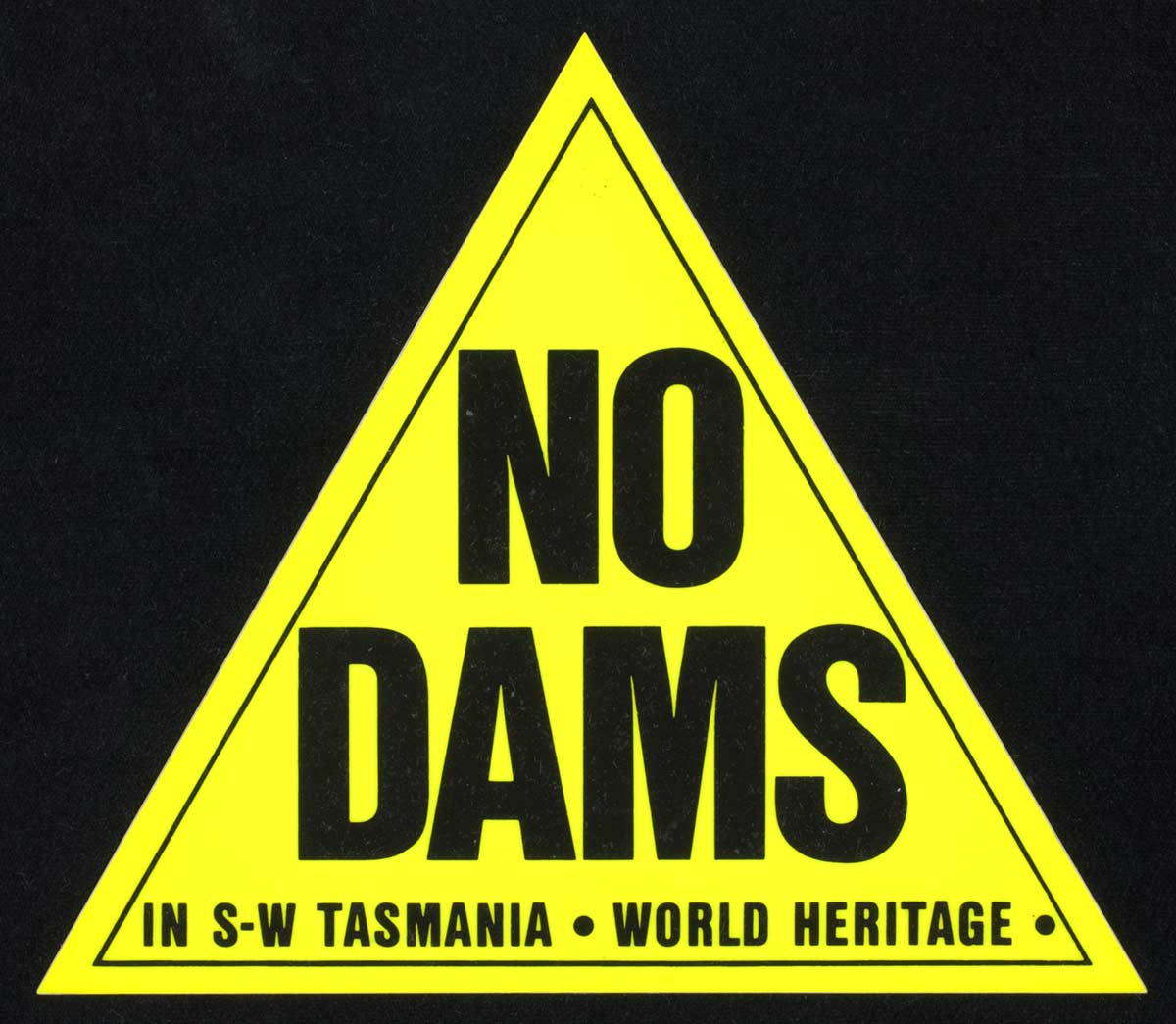 Yellow triangle on black background. Within the triangle are the words NO DAMS in capital letters. Beneath these are the words 'IN S W TASMANIA. WORLD HERITAGE. - click to view larger image